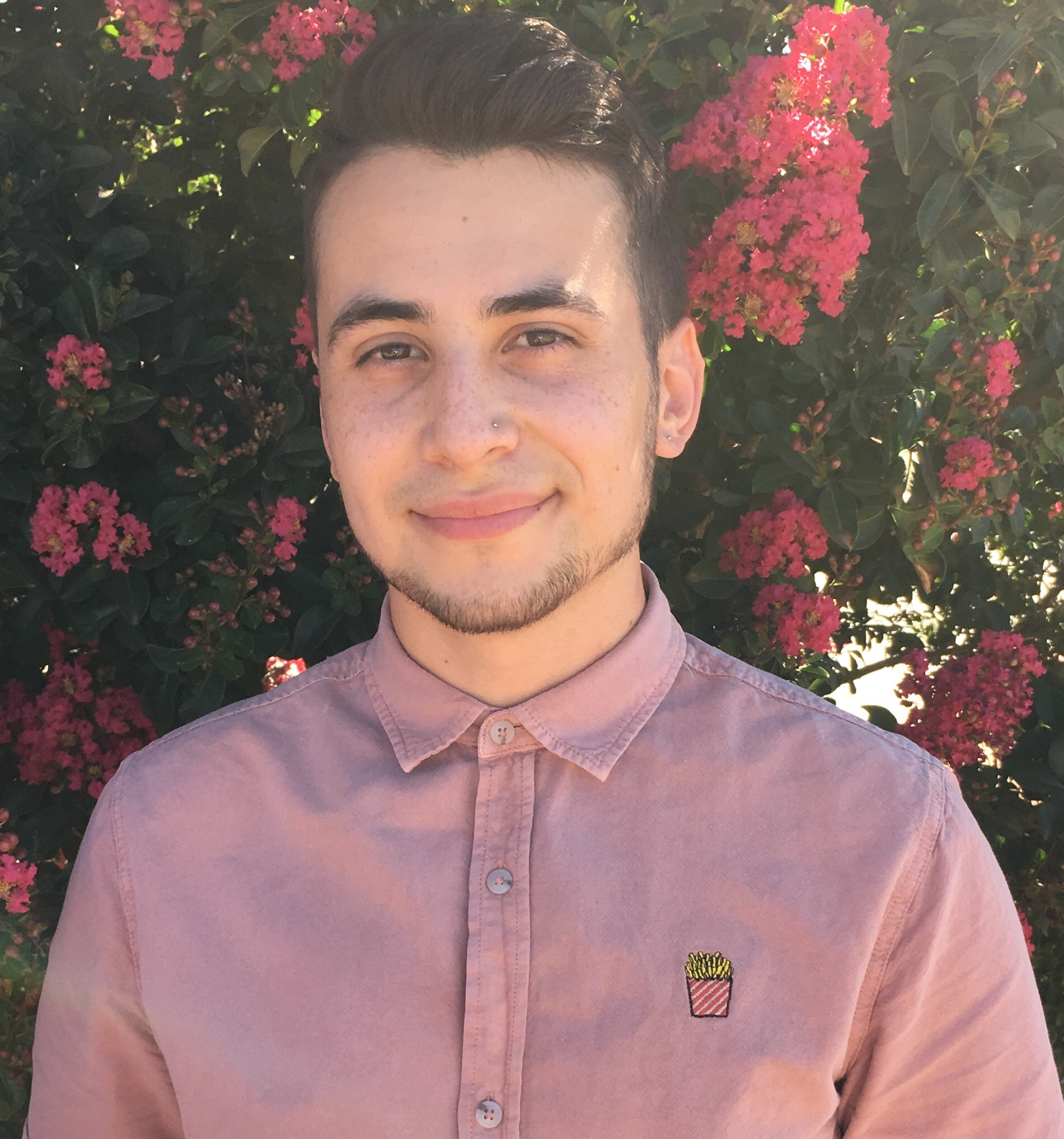 Head and shoulders photo of Angelo with a dusty rose button up top, and a small smile, with a crepe myrtle tree in the background