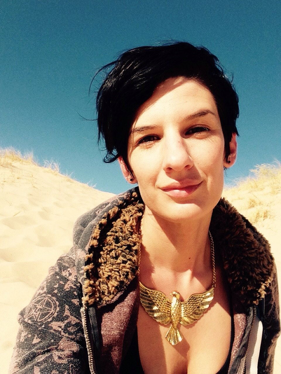 elizabeth coté sitting in Mojave sand dunes, smiling, wearing a golden hawk necklace.