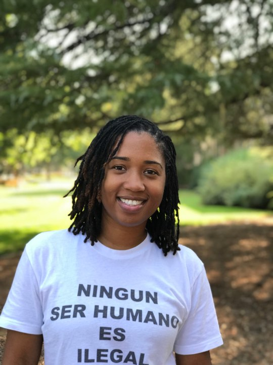 Head and shoulders photo of Monae. Monae is smiling and tree branches are in the background.  Monae's shirt reads: Ningun ser humano es ilegal.