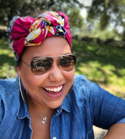 Staff member Sara is laughing into the camera wearing a pink and yellow head wrap, blue denim shirt and aviator sunglasses