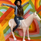 Baani, sitting on top of a unicorn statue in a room with rainbow walls. Baani is wearing denim jeans and jacket, and a black hat